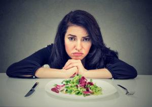Une femme qui souhaite perdre du poids est frustré face à sa salade